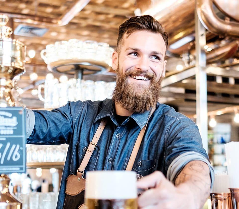 smiling man serving beer
