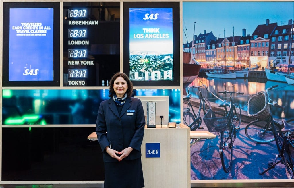 SAS employee standing in front of kiosk