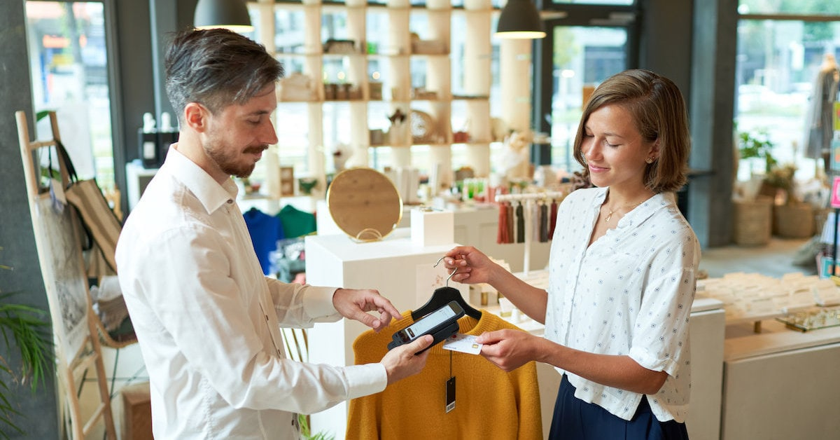 User paying in fashion store with mobile scanning